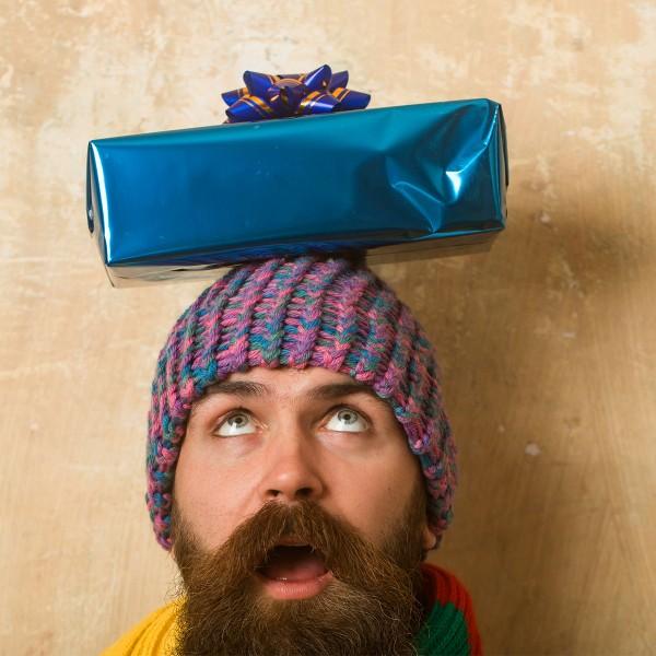 Hipster-mit-Bart-und-blauem-Geschenk-auf-dem-Kopf