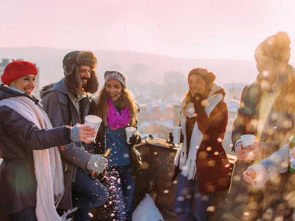 Gruppe-von-Freunden-feiert-Silvester-am-Dach-und-stossen-an