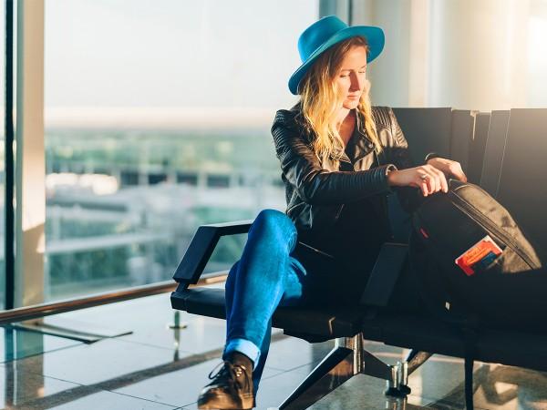 Junge-Frau-sitzt-am-Flughafen-und-wartet-auf-ihren-Flug