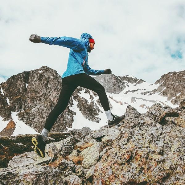 Mann-mit-blauer-Sportjacke-wandert-auf-Berg