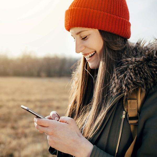 Maedchen-mit-orangener-Muetze-tippt-auf-Smartphone