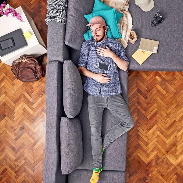 Junger-stylischer-Mann-liegt-auf-Sofa-und-schlaeft
