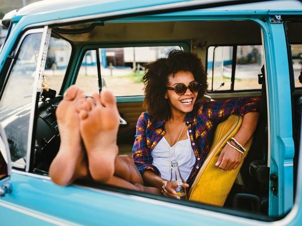Junge-Frau-sitzt-in-Auto-und-geniesst-den-Urlaub