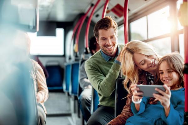 Familie-mit-Kind-und-Smartphone-sitzt-im-Bus