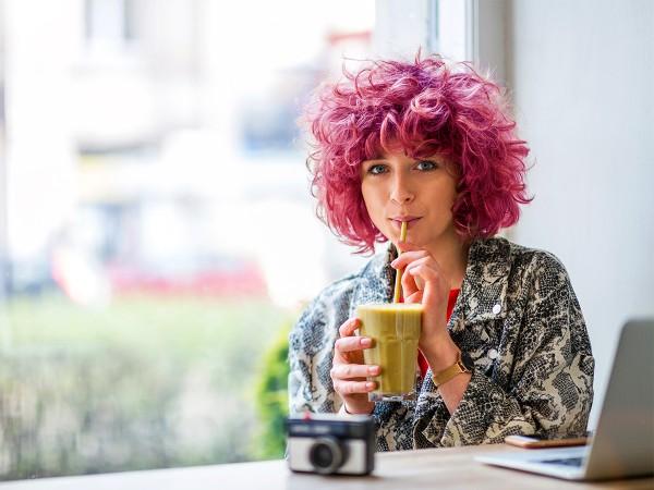 Moderne-junge-Frau-trinkt-gruenen-Smoothie