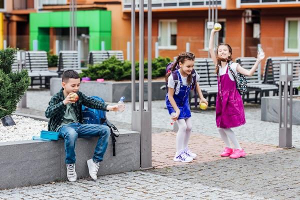 Froehliche-Schulkinder-geniessen-ihre-gesunde-Jause