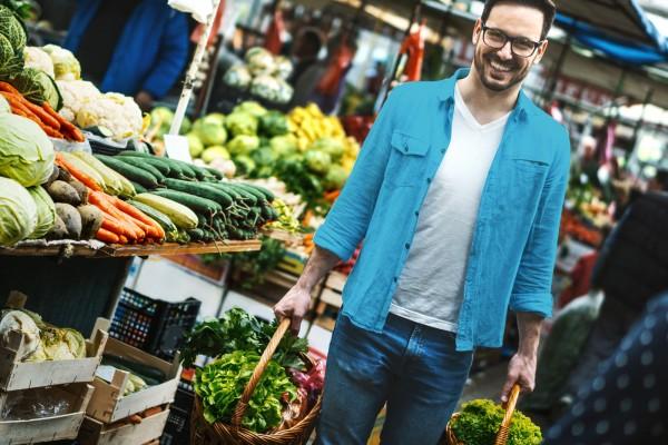 Attraktiver-Mann-mit-blauem-Hemd-und-Brille-auf-dem-Gemuesemarkt