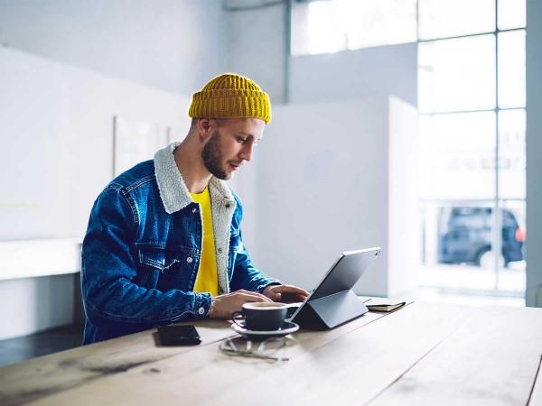 Junger-Mann-mit-gelber-Muetze-arbeitet-am-Laptop
