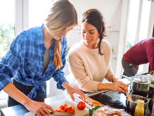 Zwei-Freundinnen-kochen-in-der-Kueche
