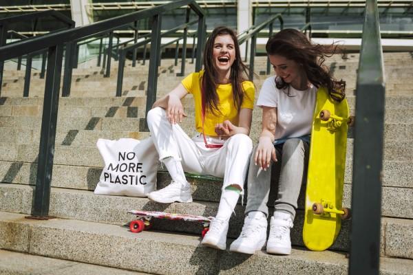 Hipster-Freundinnen-sitzen-lachend-auf-Stufen