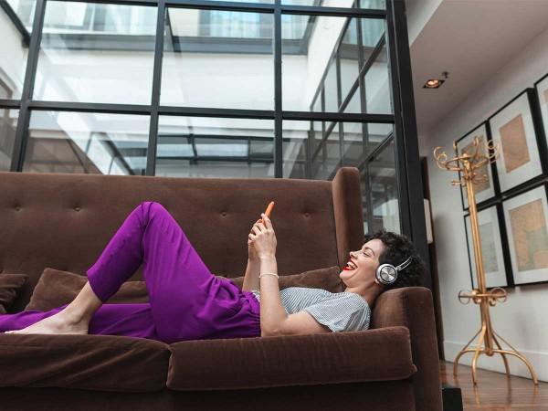 Glueckliche-jungeFrau-mit-Smartphone-und-Kopfhoerern-auf-Sofa