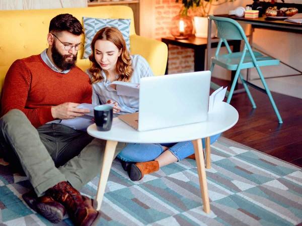 Paar-sitzt-am-Boden-vor-dem-Laptop-und-trinkt-Tee